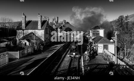 La imagen en blanco y negro de un tren a vapor en Swanage railway tomando a los pasajeros en la estación de tren el castillo Corfe, en Dorset, Reino Unido.