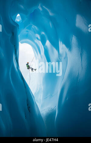 Un escalador de hielo en una chaqueta verde y naranja casco rappeles pasado una entrada grande redondeada a una cueva de hielo en el Glaciar Matanuska en Alaska.