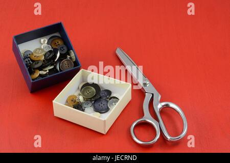 Colección de botones en cuadros blancos y azules y tijeras de metal sobre fondo de madera roja