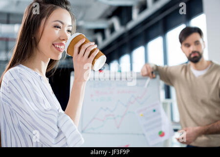 Vista lateral de la empresaria sonriente bebiendo café con su colega detrás