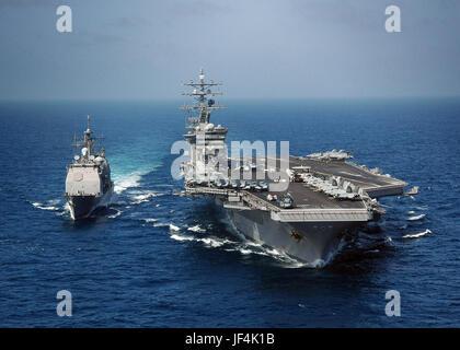 La clase Ticonderoga crucero de misiles guiados USS Bunker Hill (CG 52) viene junto con la clase Nimitz portaaviones Foto de stock