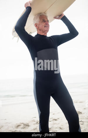 Altos hombre sujetando una tabla de surf sobre su cabeza