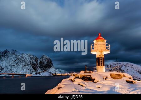 Un faro en la nieve del Ártico con la aldea de noche reine en el fondo Nordland Islas Lofoten Noruega Europa
