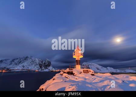 El faro y la luna llena en el Ártico con la aldea de noche reine en el fondo Nordland Islas Lofoten Noruega Europa