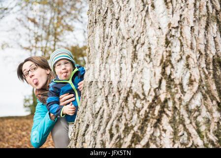 Madre e hijo que sobresalen heredero salones mirando detrás del gran árbol en el paisaje del otoño