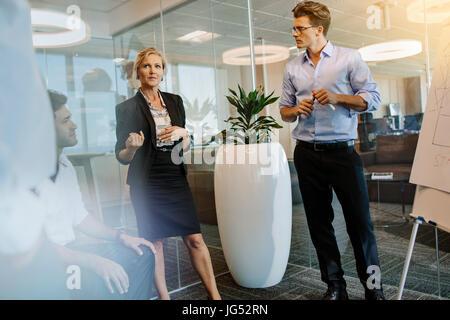 Empresaria madura discutiendo con sus colegas durante la presentación en la oficina moderna. Gente de negocios tras una reunión en la oficina.