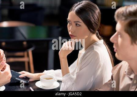 Equipo empresarial en reunión discutiendo proyecto en café, almuerzo de negocios concepto