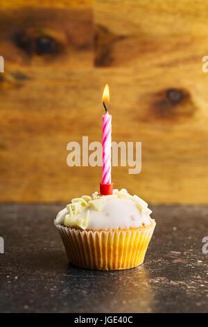 Cupcake con velas encendidas en la mesa.