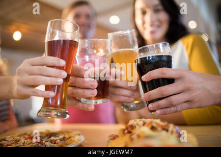 Ángulo de visión baja de feliz amigos bebidas tostado en una mesa en el restaurante