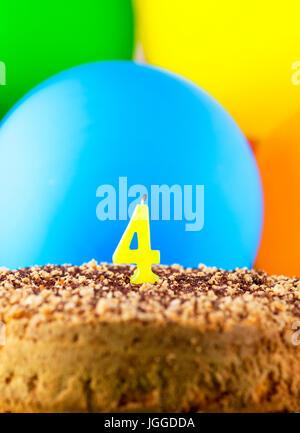 Torta casera con número cuatro velas y globos de fondo.