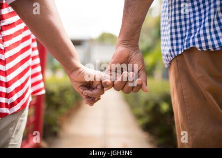 Imagen recortada de alto par la celebración de dedos pequeños mientras está de pie en el patio