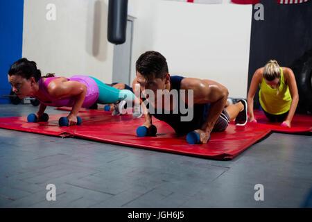 Los jóvenes atletas masculino y femenino practicando empuje ups en pesas en el gimnasio Foto de stock