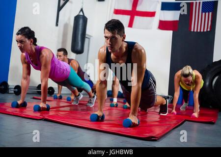 Los jóvenes deportistas practicando empuje ups en pesas en el gimnasio Foto de stock