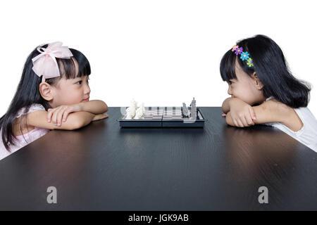Chino Asia hermanitas jugando ajedrez juntos en casa.