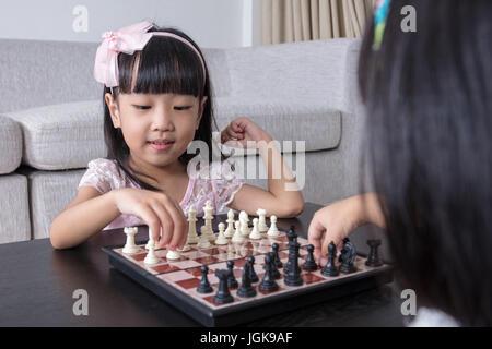 Chino Asia hermanitas jugando ajedrez juntos en el salón de casa.