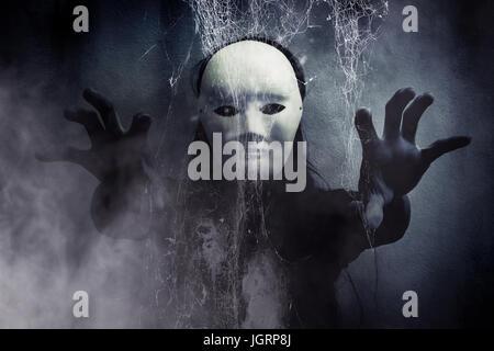 Misteriosa mujer vestidos de blanco en negro oculto detrás de la máscara de tela de araña,Scary antecedentes para la portada del libro.
