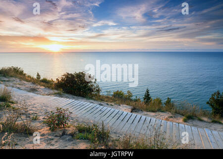 Puesta de sol sobre el Lago Michigan brilla boardwalk en Empire Bluff Trail cerca de Empire en Michigan. Este sendero da oso dormido dunas Foto de stock