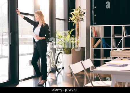 Seguro joven empresaria holding tableta digital y mirando en la ventana en la oficina moderna