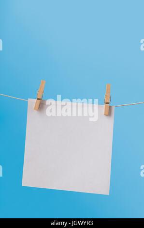 Una sola hoja de papel blanco, cuadrado, colgando de una línea de ropa en perchas de madera contra un cielo azul claro. Dejar en blanco para copiar el espacio.
