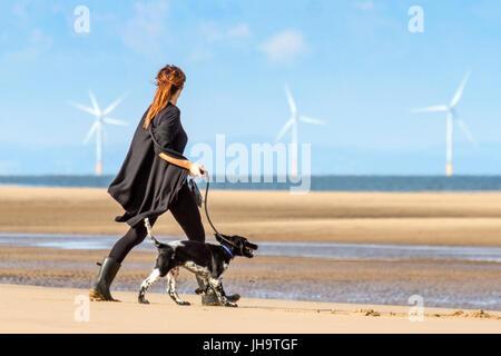 Caminante de perros en la playa Southport, Merseyside, 13 de julio de 2017. El tiempo en Reino Unido. Un hermoso y soleado comienzo del día en la costa noroeste de Inglaterra, ya que los senderistas de perros llevan a sus queridos animales para correr al sol en la arena dorada de la playa de Southport en Merseyside. Con un magnífico pronóstico de sol que continuará durante todo el día, se espera un día encantador en el popular complejo costero. Crédito: Cernan Elias/Alamy Live News