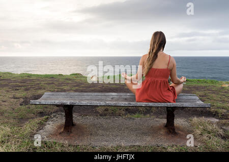 Una mujer en un vestido naranja medita sobre un banco de madera junto al mar.