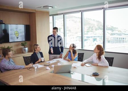 Socios de negocios jóvenes discutiendo en la reunión en la sala de oficina Foto de stock