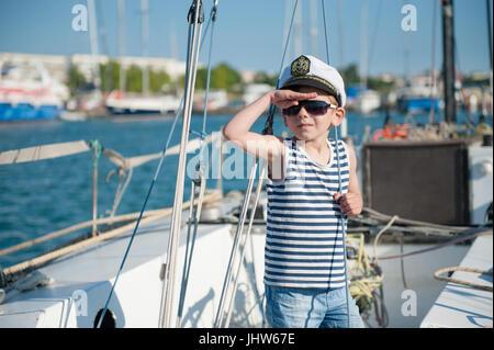 ... Cute little boy capitán capitán vistiendo gorra y gafas de sol a bordo  de la embarcación 70ae0bf8c1c