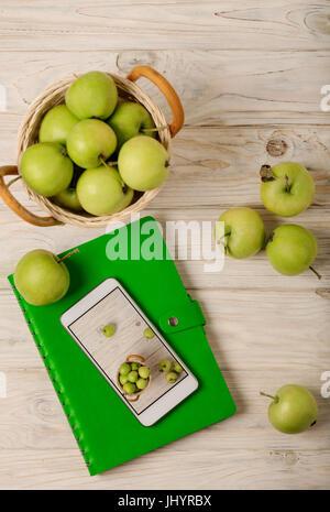 Las manzanas verdes en una canasta, verde portátil y teléfono blanco sobre un fondo de madera ligera. El enfoque selectivo.