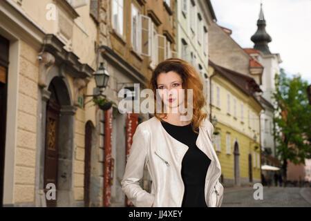 Mujer Bonita de pie en la calle de adoquines de la plaza superior con St Florian's campanario en la parte vieja de la ciudad de Ljubljana, capital de Eslovenia Europa Foto de stock