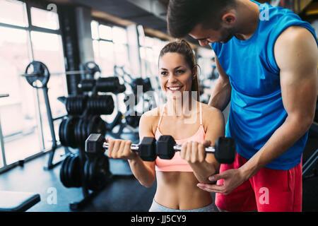 Bella mujer haciendo ejercicios en el gimnasio con entrenador personal