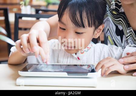 Chino Asia niña jugando tablet pc con su madre en la cafetería al aire libre