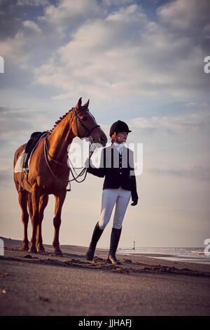 Una joven mujer de pie con su caballo en la playa. Foto de stock