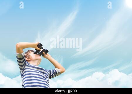 Chico mirando a través de binoculares contra sky