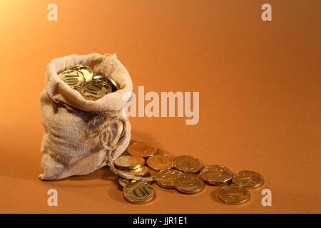 Concepto de riqueza. Abra la arpillera saco lleno de monedas de oro de pie sobre fondo naranja