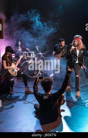 Joven mujer sentados en el escenario y fotografiar la banda de rock and roll