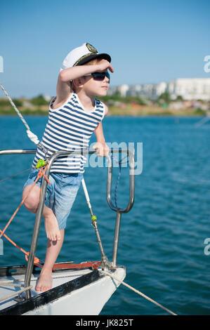 ... verano soleado día en puerto  Cute little capitán pequeño niño usando  el capitán sombrero y gafas de sol de moda igualitarios b2c2827a771