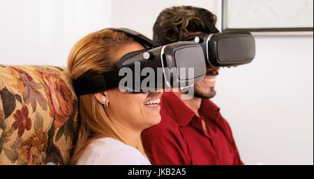 Feliz pareja blanca en casa. Los jóvenes hispanos hombre y mujer sentada en un sofá jugando con gafas de realidad virtual, tecnología VR gafas.