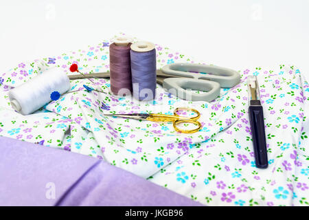 Una selección de accesorios de costura, como tijeras, algodón, con tejido normal y patrón aparece sobre fondo blanco.