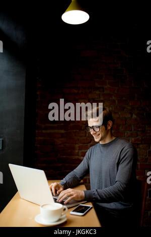 Retrato de un hombre joven con el portátil en la tienda de café Foto de stock