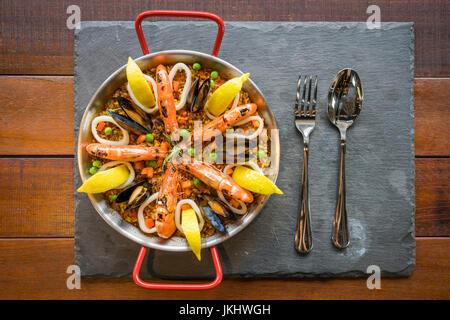 Paella de marisco con verduras y azafrán servido en el tradicional pan vista desde arriba.