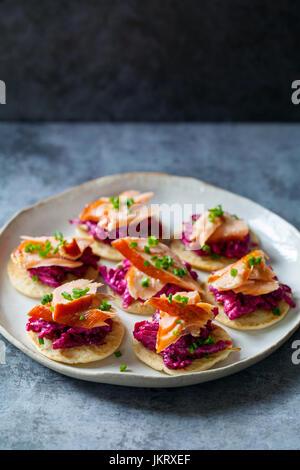 Blinis con remolacha, rábano picante, salmón ahumado en caliente y cabra chhese