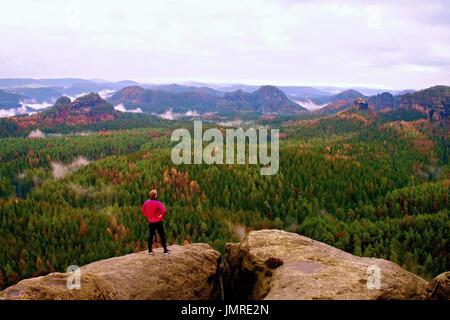 Runner en rosa chaqueta y pantalón negro de luz. Corta el jengibre al hombre en su destino. Cansado deportista tome un descanso en la ruta de las Montañas Rocallosas.