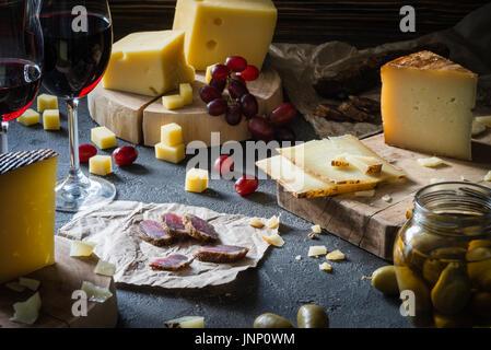 Tabla de quesos de quesos duros picado (en sueco, castellano manchego) y rebanadas italiano pecorino toscano sobre tablas de madera, con aceitunas verdes en vidrio ja