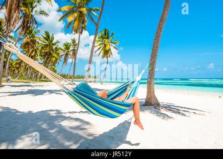 Canto de la playa, Isla Saona, East National Park (Parque Nacional del Este), en la República Dominicana, Mar Caribe. Mujer relajándose en una hamaca.