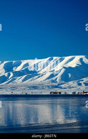 Falls Dam y gama Hawkdun en invierno, Maniototo, Central Otago, Isla del Sur, Nueva Zelanda Foto de stock