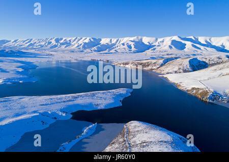 Hielo en el borde de Falls Dam, y en invierno, Gama Hawkdun Maniototo, Central Otago, Isla del Sur, Nueva Zelanda Foto de stock