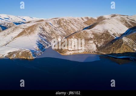 En el borde del hielo cae presa en invierno, Maniototo, Central Otago, Isla del Sur, Nueva Zelanda - antena drone Foto de stock