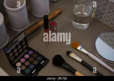 Un alto ángulo de visualización de productos de belleza con vaso para beber en la mesa