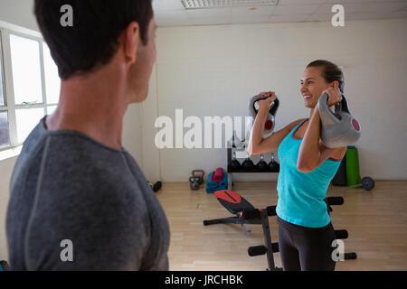 Formador macho mirando la atleta femenina kettlebells de elevación en el club