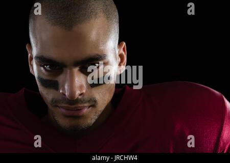Retrato de determinado jugador de fútbol americano contra un fondo negro